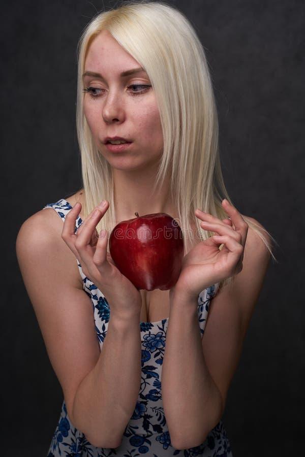 Schönes Mädchen in einer modischen Kleidung mit Apfel lizenzfreies stockbild