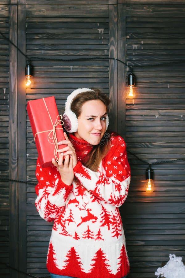 Schönes Mädchen in einer roten Strickjacke welchen inneren Weihnachtskasten wundernd stockfoto