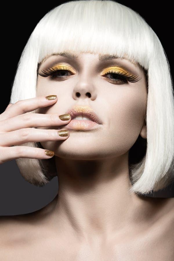 Schönes Mädchen in einer weißen Perücke, mit Goldmake-up und Nägeln Feierliches Bild Schönes lächelndes Mädchen lizenzfreies stockfoto