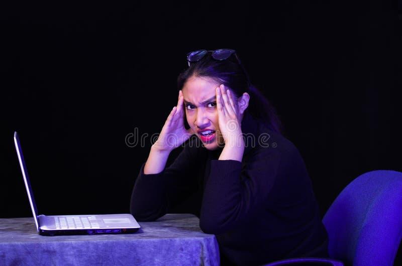 Schönes Mädchen erhielt vor ihrem Laptop auf dunklem Hintergrund stressig stockfotografie