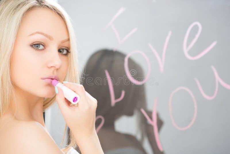 Schönes Mädchen geschrieben auf einen Spiegel in Lippenstift, I stockfoto