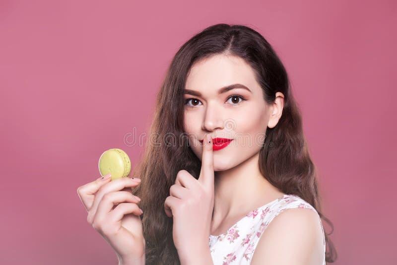 Schönes Mädchen hält eine Makrone und zeigt Zeichen auf einem rosa Hintergrund lizenzfreies stockfoto