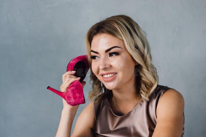 Schönes Mädchen hält einen rosa Schuh in ihrer Hand stockbilder