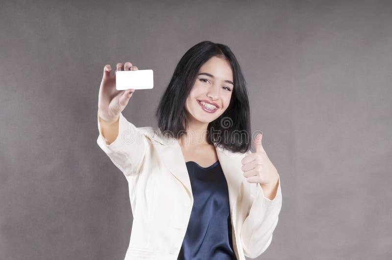 Schönes Mädchen hält heraus Visitenkartestudiomarketing-Klammern lizenzfreie stockfotos