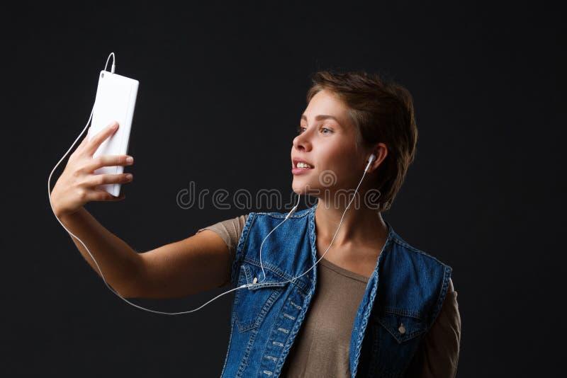 Schönes Mädchen hört Musik mit ihrem Telefon auf einem schwarzen Hintergrund lizenzfreie stockfotografie