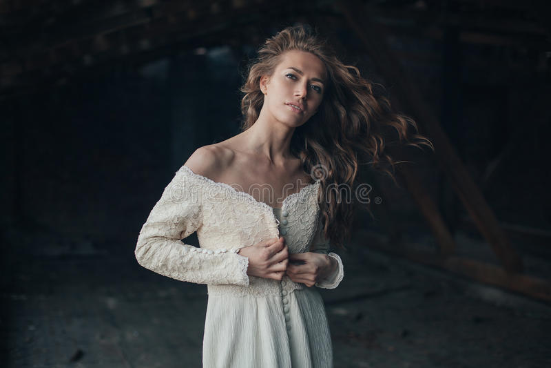 Schönes Mädchen herein im weißen Weinlesekleid mit dem gelockten Haar, das auf dem Dachboden aufwirft Frau im Retro- Kleid Besorg lizenzfreies stockfoto