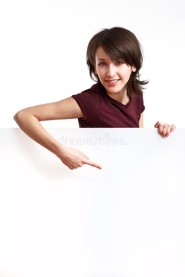 Schönes Mädchen hinter einem leeren weißen Vorstand stockbild