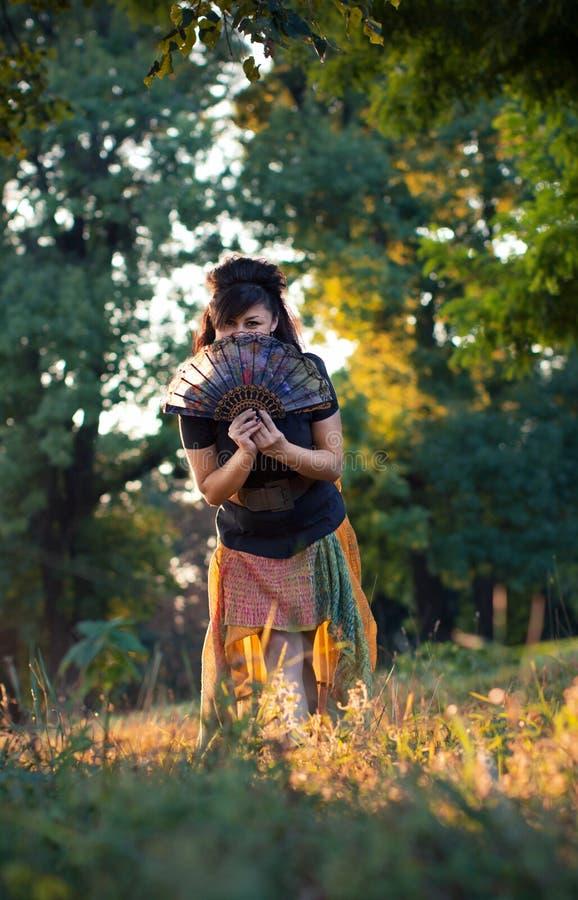 Schönes Mädchen hinter traditionellem Fan lizenzfreie stockfotografie
