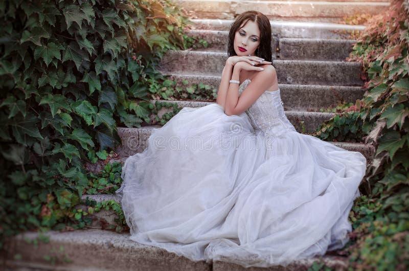 Schönes Mädchen im üppigen Kleid im Garten Attraktive Brunettefrau in einem langen weißen Kleid, sitzend in blühenden Rosen eines stockfotografie
