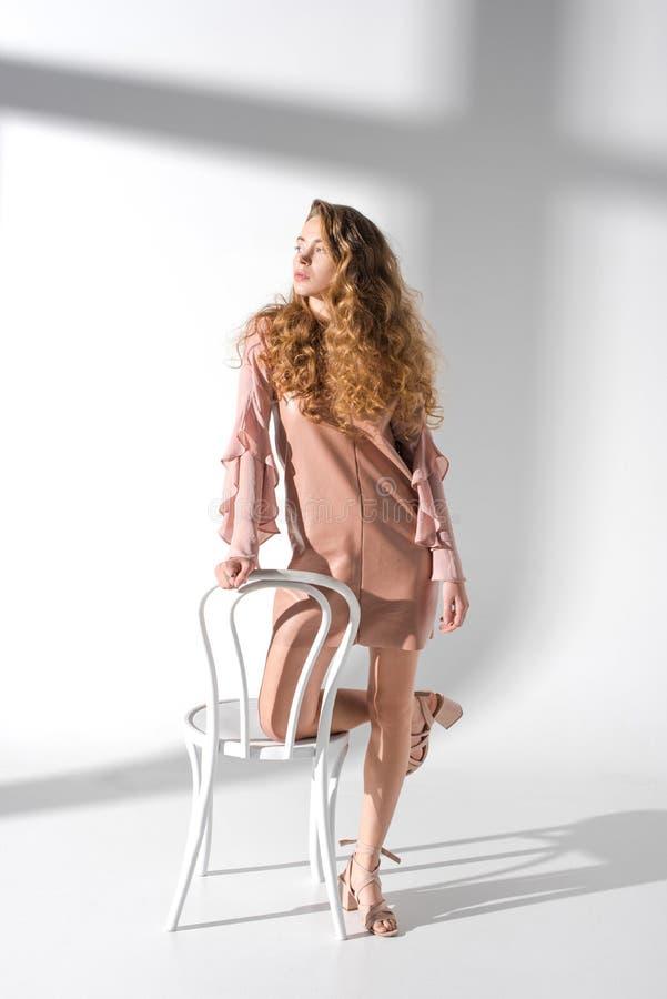 schönes Mädchen im beige Kleid, das auf Stuhl mit einem Knie sich lehnt stockfoto