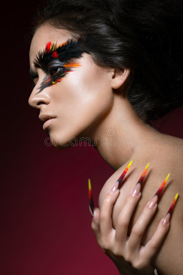 Schönes Mädchen im Bild von Phoenix-Vogel mit kreativem Make-up und langen Nägeln Maniküredesign Schönes lächelndes Mädchen stockfotografie
