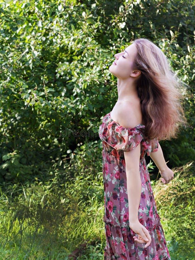 Schönes Mädchen im Blumenkleiderstand im Garten. lizenzfreie stockbilder