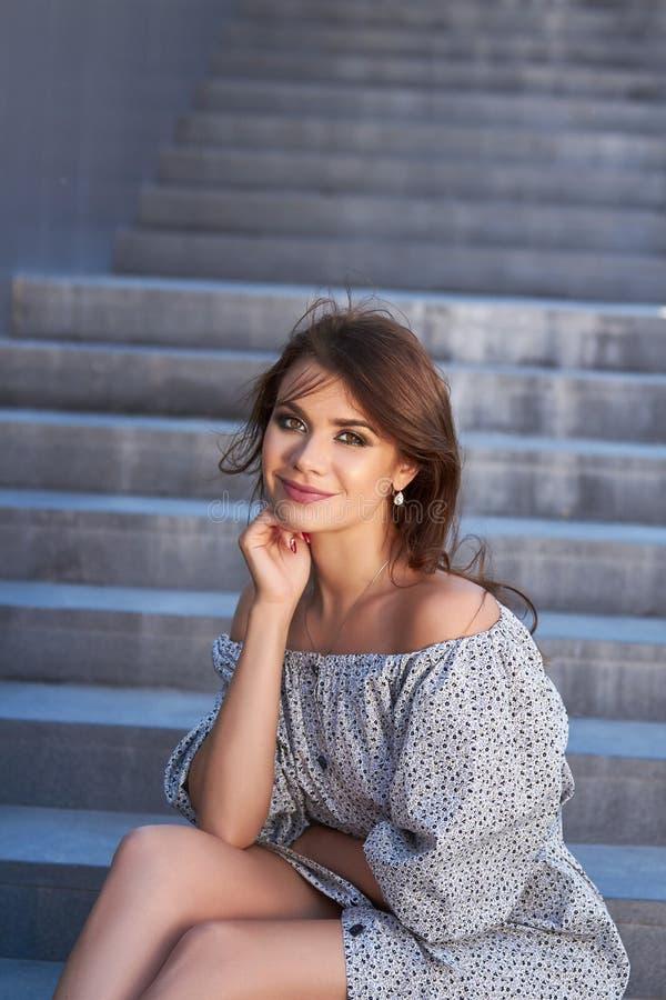 Schönes Mädchen im eleganten Kleid und reizend im Lächeln, die für den Fotografen in der Stadt von Jekaterinburg aufwirft lizenzfreies stockbild