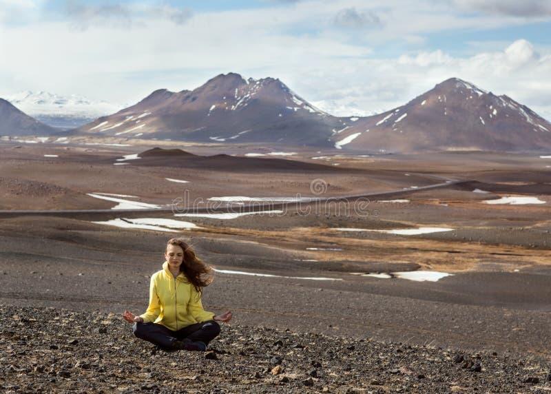 Schönes Mädchen im Gelb nimmt an Yoga in den Bergen von teil stockbilder
