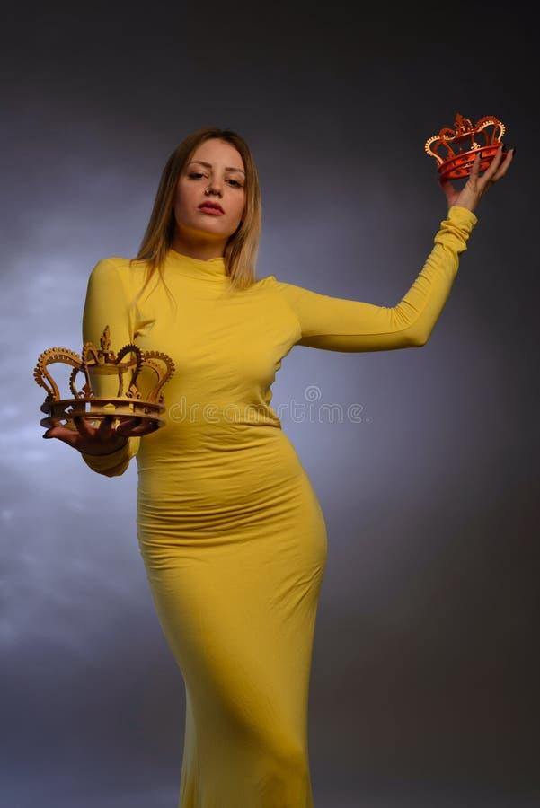 Schönes Mädchen im gelben Abendkleid schlägt vor, eine Krone an zu versuchen lizenzfreie stockfotos