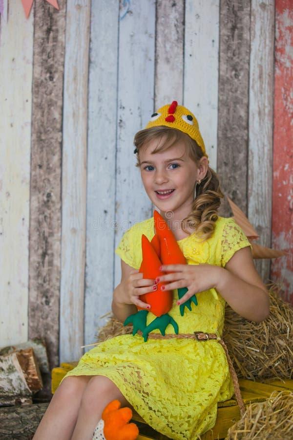 Schönes Mädchen im gelben Kleid, spielend mit Karotte stockfotografie