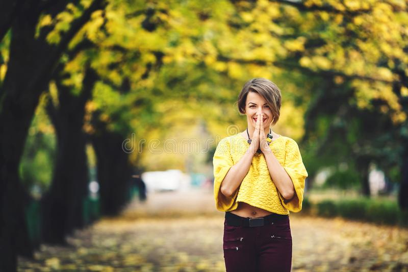Schönes Mädchen im Herbst steht auf Gasse mit gelben Ahornen und hält ihre Hände nahe ihrem Mund mit Lächeln stockbild