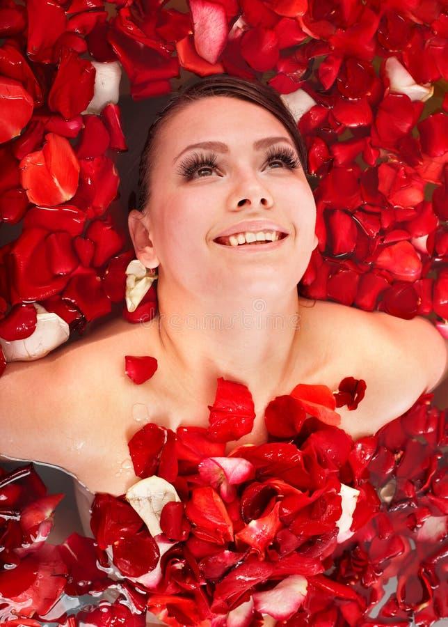 Schönes Mädchen im Jacuzzi mit dem rosafarbenen Blumenblatt. stockbilder