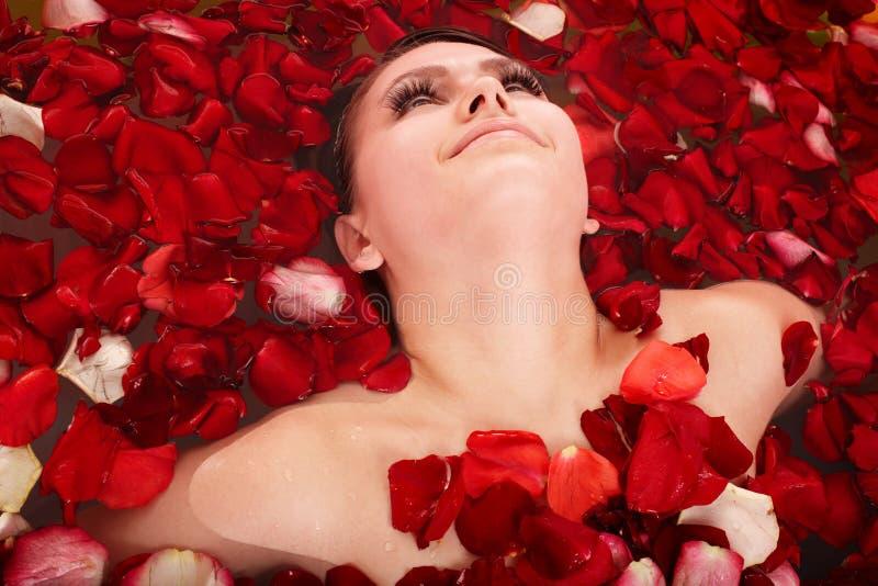 Schönes Mädchen im Jacuzzi mit dem rosafarbenen Blumenblatt. lizenzfreies stockfoto