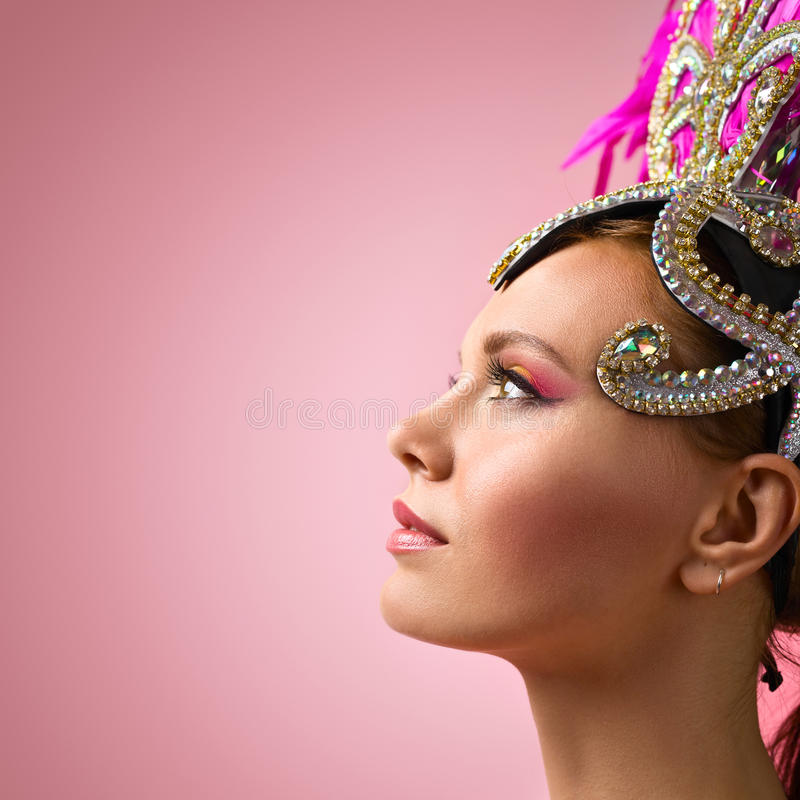 Schönes Mädchen im Karnevalskopfschmuck auf rosa Hintergrund stockfoto