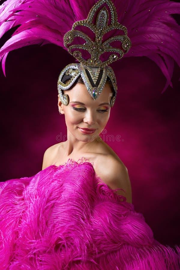 Schönes Mädchen im Karnevalskostüm mit rosa Federn stockfotos