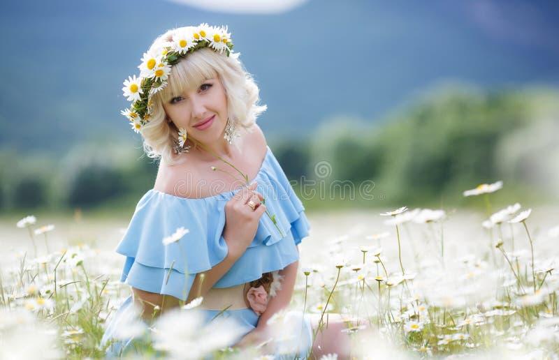 Schönes Mädchen im Kleid auf dem Gänseblümchenblumenfeld lizenzfreie stockbilder