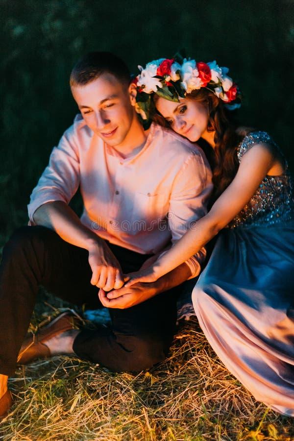 Schönes Mädchen im Kleid mit dem Kranz, der ihren Kopf auf die Schulter des netten Kerls draußen hinsetzend nachts setzt lizenzfreie stockbilder