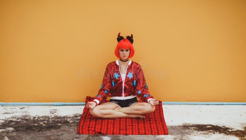 Schönes Mädchen im Kostüm des roten Teufels, das in der Yogahaltung in Erwartung Halloweens sitzt Trägt eine rote Perücke und Hör lizenzfreie stockfotos