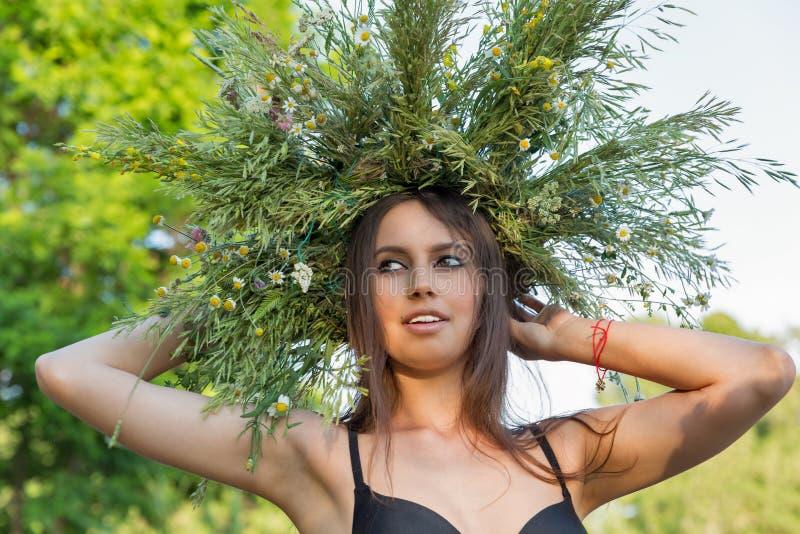 Schönes Mädchen im Kranz des Porträts der wilden Blumen stockfotografie
