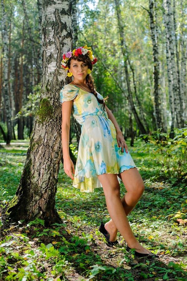 Schönes Mädchen im Kranz von Blumen nähern sich Birke stockfoto