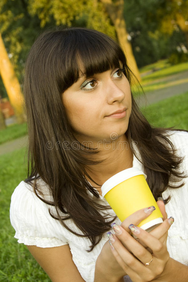 Schönes Mädchen im Park mit Kaffee lizenzfreie stockfotos
