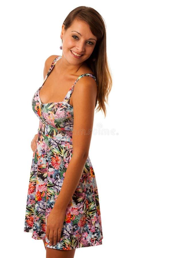 Schönes Mädchen im patern kurzen Sommerkleid der Blume, das gegen Weiß aufwirft stockfotografie