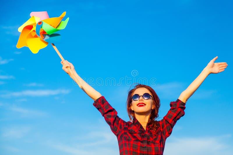 Schönes Mädchen im Plaidkleid mit Windspielzeug lizenzfreie stockbilder