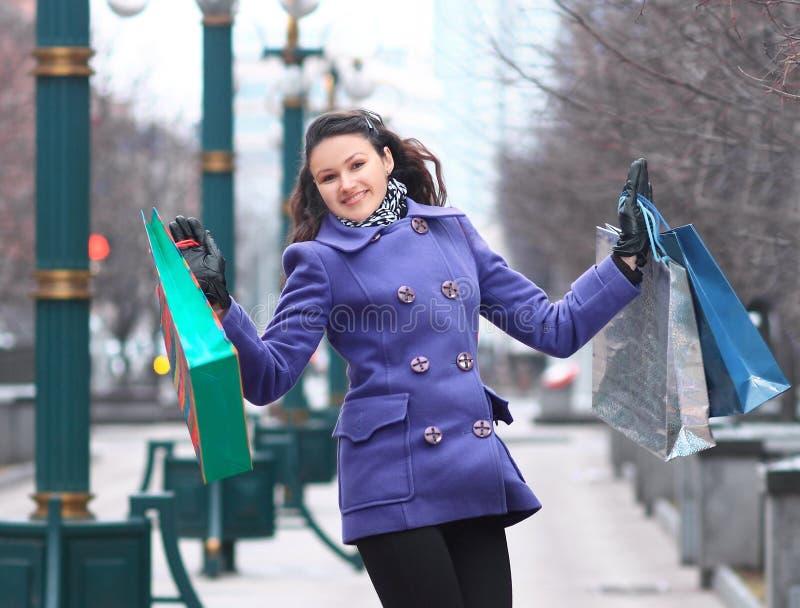 Schönes Mädchen im purpurroten Mantel mit dem Einkaufen auf der Straße stockbild