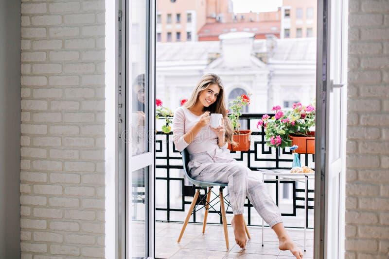 Schönes Mädchen im Pyjama, der auf Balkon zu Hause morgens frühstückt Sie h?lt eine Schale und das L?cheln zur Kamera lizenzfreie stockfotos