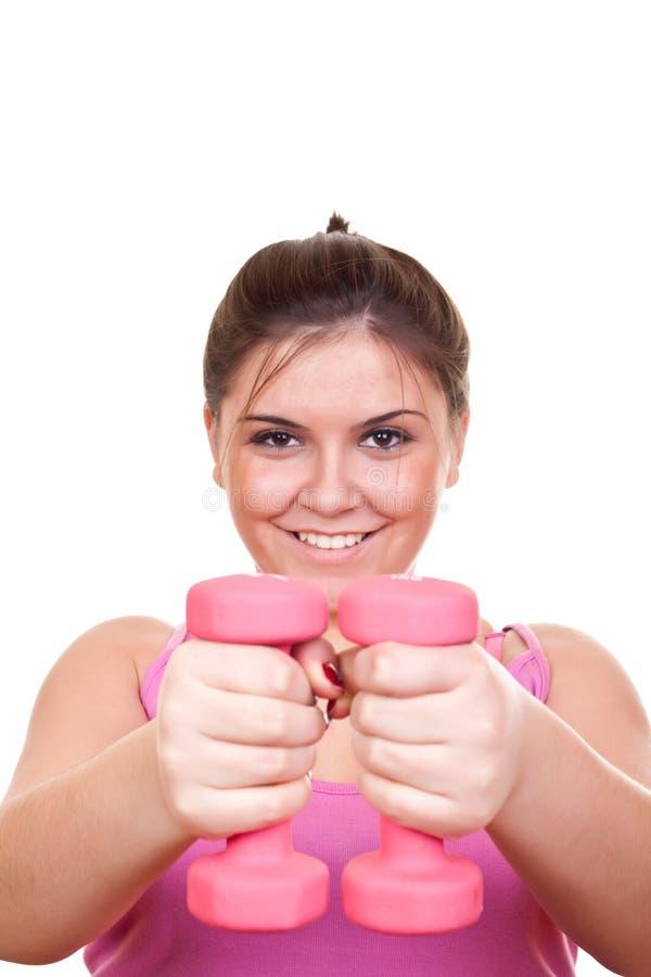 Schönes Mädchen im rosafarbenen Holdinggewicht für Übung stockbilder