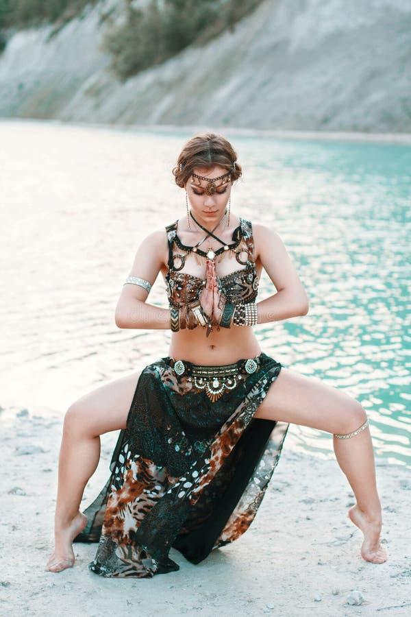 Schönes Mädchen im Stammes- Fusionskostüm, das in einer Haltung auf Th steht stockfoto