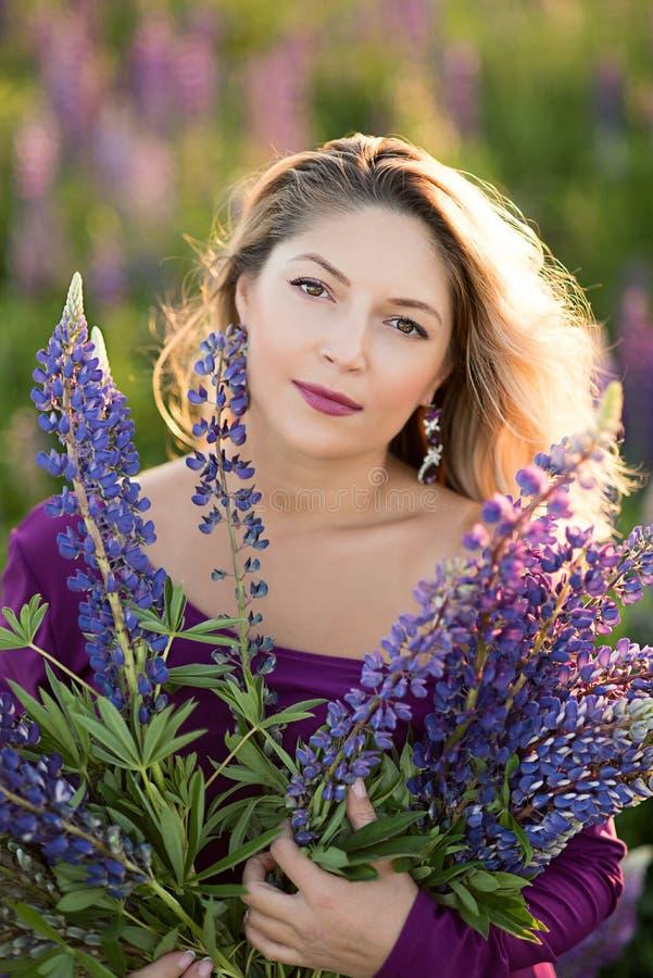 Schönes Mädchen im violetten Kleid, das einen Lupine bei Sonnenuntergang auf dem Feld hält Das Konzept der Natur und des Romance lizenzfreies stockfoto