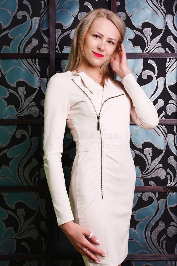 Schönes Mädchen im weißen eng anliegenden Kleid, das nahe Wand der Tapete aufwirft lizenzfreie stockfotos