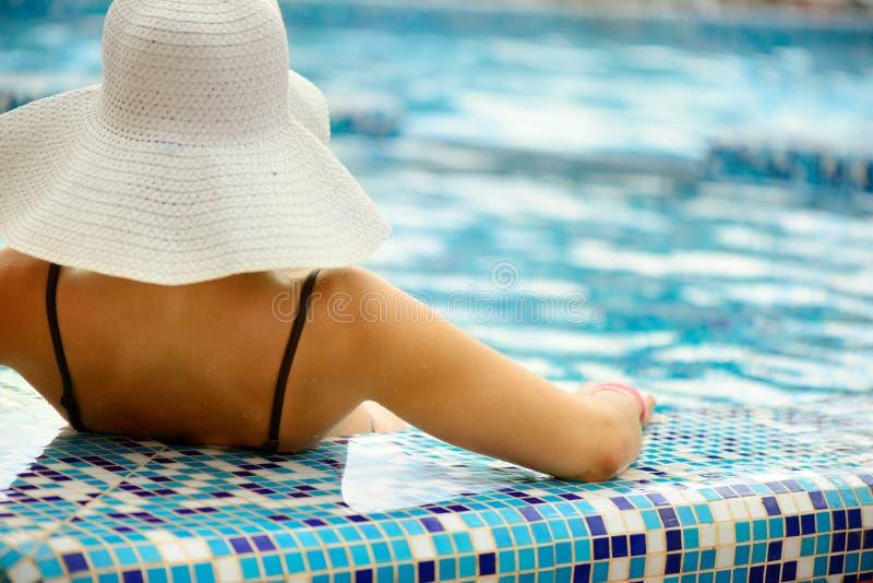 Schönes Mädchen im weißen Hut, der am Swimmingpool sich entspannt stockbild
