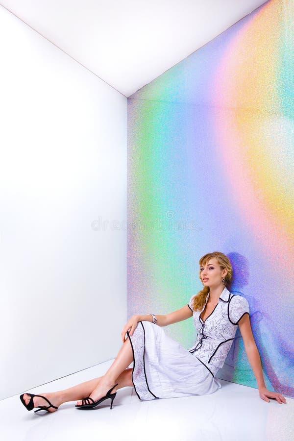 Schönes Mädchen im weißen Kleid, das auf Fußboden sitzt stockbild