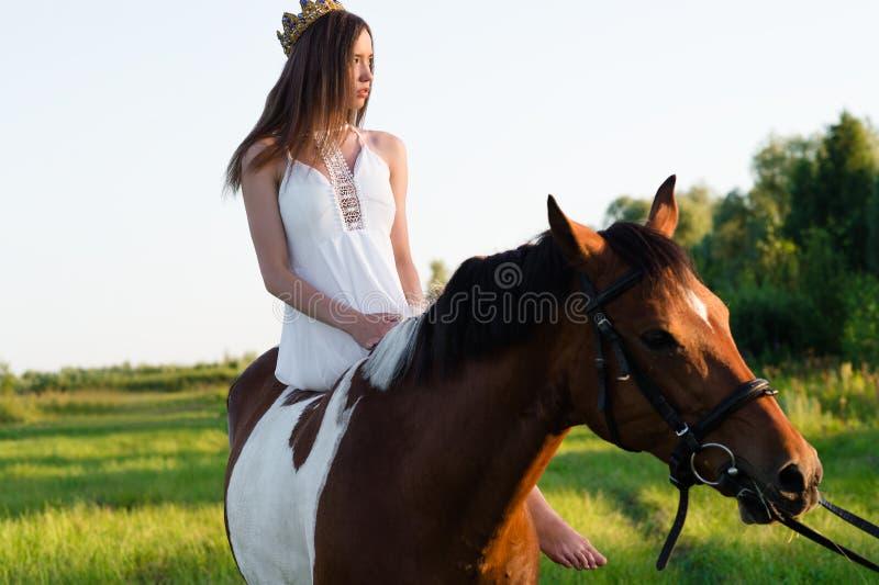 Schönes Mädchen im weißen Kleid, das auf Pferd sitzt stockfoto