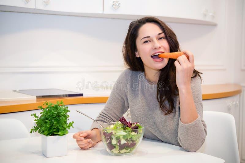 Schönes Mädchen isst Karotte und Salat lizenzfreie stockbilder