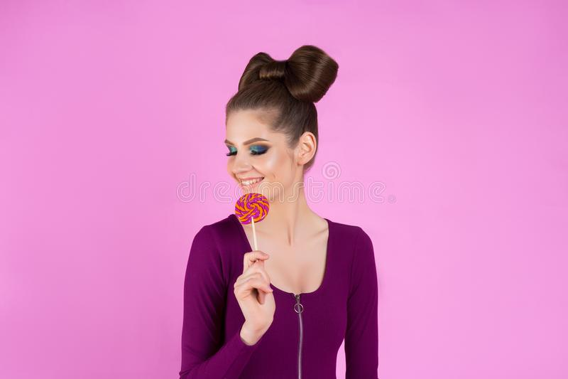 Schönes Mädchen isst Süßigkeit auf einem Stock auf einem lokalisierten rosa Hintergrund Werbung für einen Konditor ` s Shop stockbild
