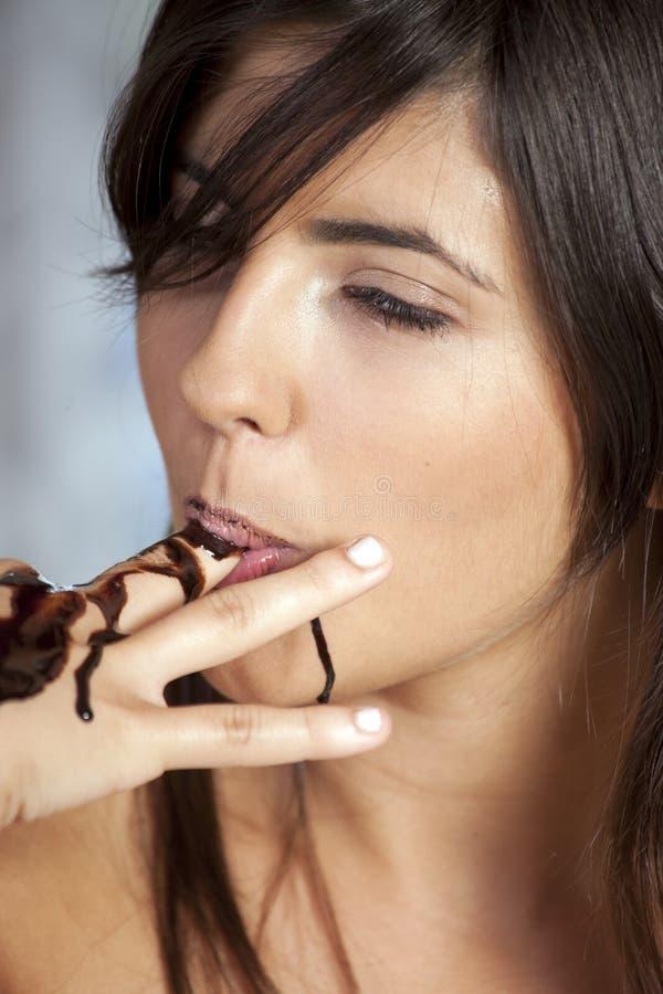 Schönes Mädchen isst Schokolade lizenzfreies stockbild