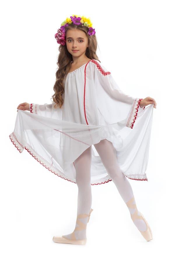 Schönes Mädchen jugendlich in der weißen Kleidung auf Pointe mit dem braunem Haar und Kranz von den Blumen lokalisiert auf weißem stockfoto