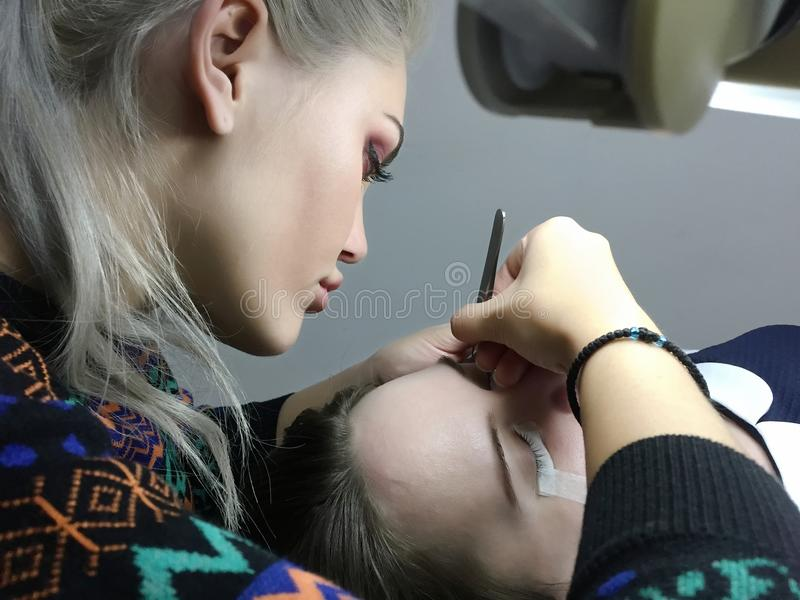 Schönes Mädchen klebt Wimpern zum Kunden im Studio stockfoto