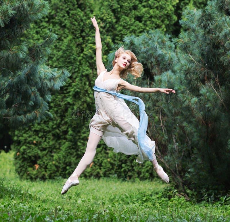 Schönes Mädchen kleidete in einem Kittel an, der in Sommerpark springt stockfoto