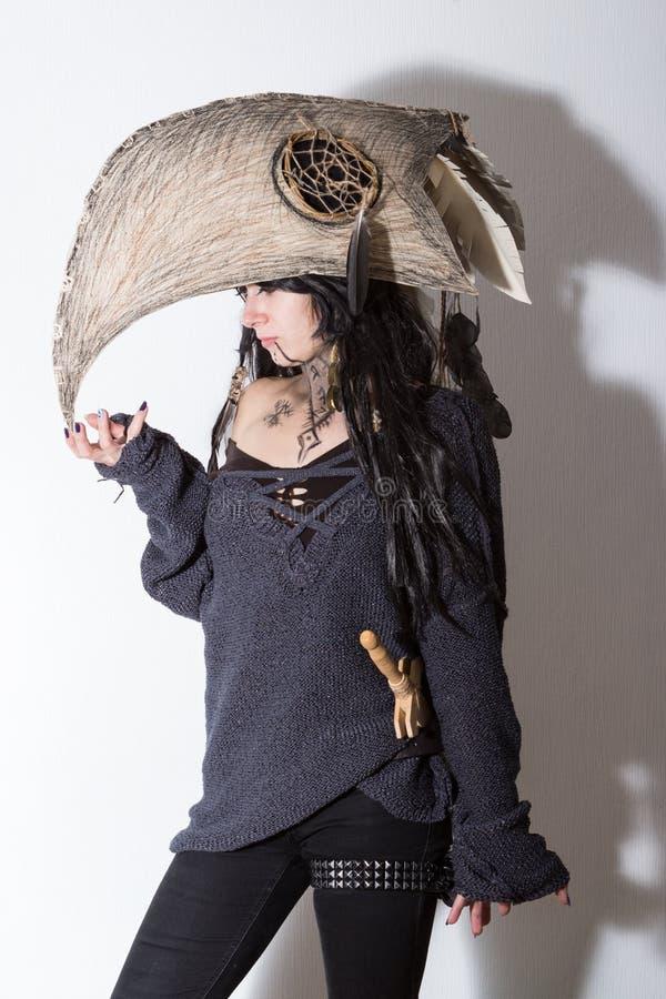 Schönes Mädchen kleidete in Hexen- oder Medizinmannhalloween-Kostüm mit schwarzen Federn und im Krähenkopf auf dem weißen Hinterg lizenzfreie stockfotografie