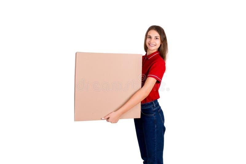 Schönes Mädchen liefert ein enormes Paket an einen Kunden Lächelnde Frau in der Arbeitskleidung hält einen Kasten lokalisiert auf lizenzfreie stockfotos